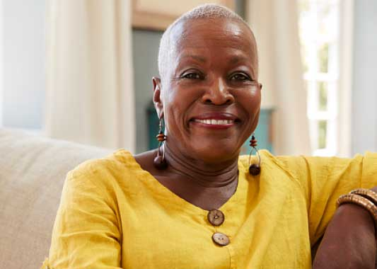 Image of a middle-aged African-American woman sitting on a couch and smiling at the camera